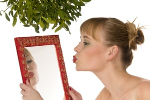 Naked model kissing herself in a mirror under mistletoe isolated on white